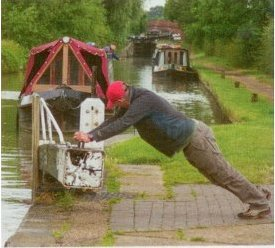 A gentleman puts his back into a lock gate